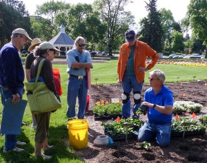 CSU research associate David Staats (kneeling) explains the planting process to Larimer County master gardeners, including (from left) Jim Carroll, Paula Mann, Gerry Hoffman (in straw hat), Daniel Owen, Craig Seymour and Karen Halberg (hidden behind Jim).